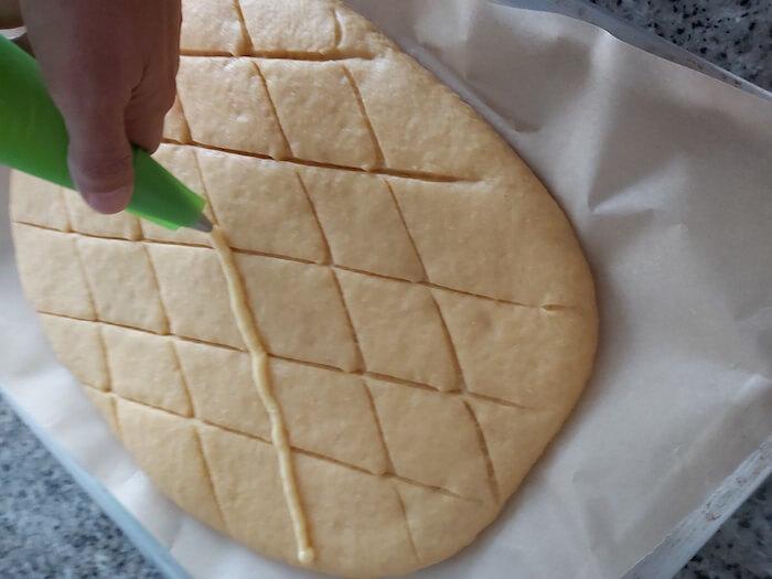 Coloca la crema pastelera sobre los cortes de la masa de coca de san juan