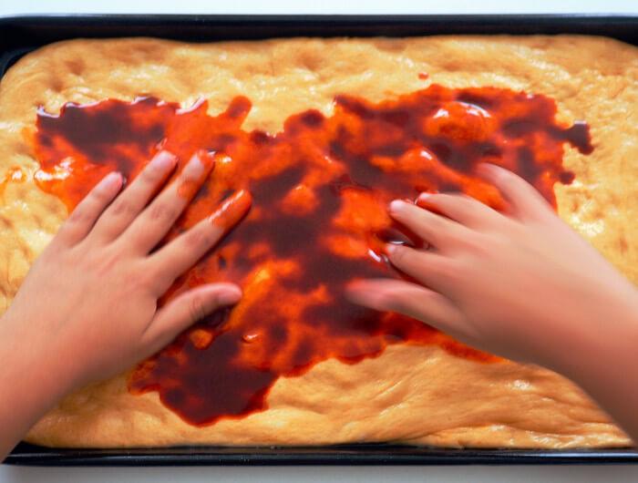 Extender la mezcla de pimentón y aceite sobre la masa